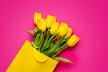 bunch of beautiful yellow tulips in cool yellow shopping bag on the wonderful pink background