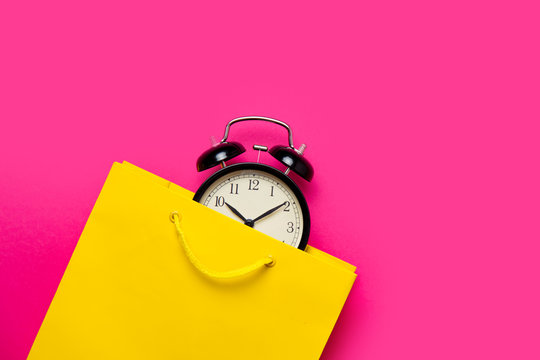 cool black alarm clock in beautiful yellow shopping bag on the wonderful pink background