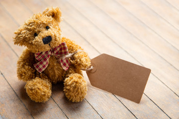 cute fluffy teddy bear with label on the wonderful brown wooden background