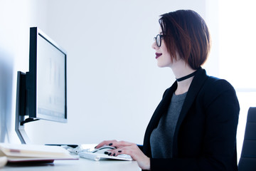 beautiful young woman sitting at the desk and typing in the cool bright office