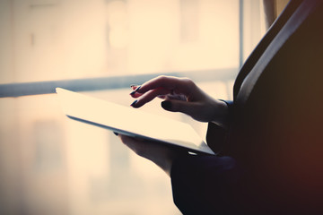 young caucasian female hands holding a tablet and typing text near the window