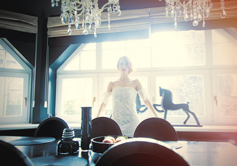 beautiful young woman standing near the table in the light luxury room