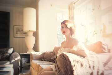 beautiful young woman sitting on the sofa in the light luxury room