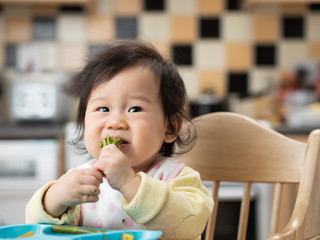 baby eating vegetable at home