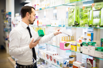 Positive man customer browsing rows of drugs