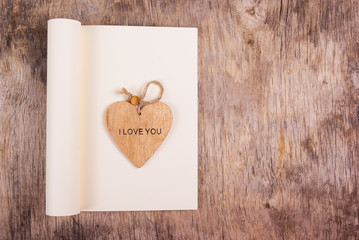Wooden heart on the background of an open diary with a blank page. Heart and notebook on a wooden background. Copy space.
