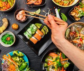 Man hand with chopsticks, eating asian food