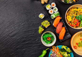 Asian food served on black stone, top view, space for text