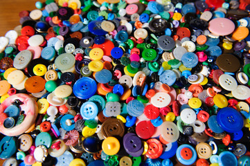 Lot of colorful plastic clothing buttons. Many small round vintage buttons pattern background