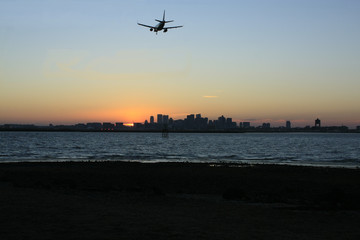 Night Flight: The airliner is approaching Boston's Logan International Airport across Boston Harbor as the sun sets behind the skyline of Boston.