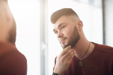 the young guy looks in the mirror and touching a hand to his beard