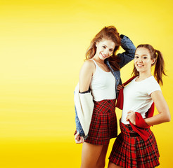 lifestyle people concept: two pretty school girl having fun on yellow background, happy smiling students