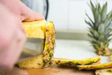 Male hands peeling fresh pineapple skin