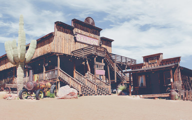 Vintage Old Wild West desert cowboy town with cactus and saloon