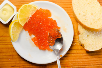 Red caviar with lemon, bread and butter on wooden board white table background. Close up image of delicacy food luxury lifestyle