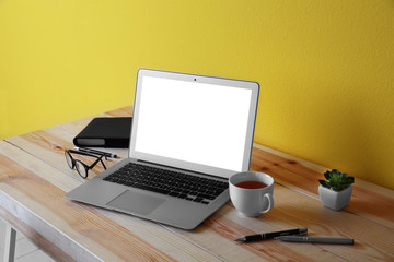 Workplace with laptop against yellow wall background