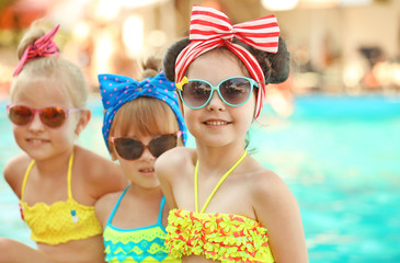 Fashionable little girls at swimming pool on sunny day