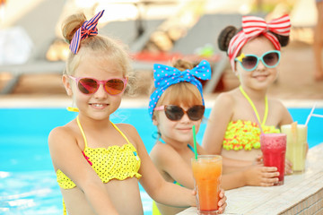 Little girls with cocktails in swimming pool on sunny day