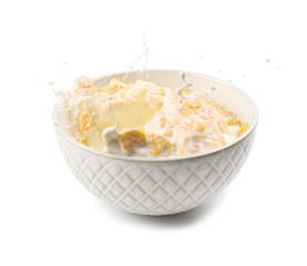 Corn flakes in bowl with milk splash on white background