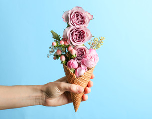 Female hand holding waffle cone with composition of flowers and branches on color background