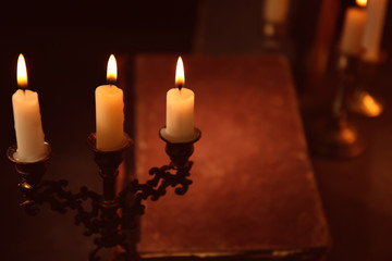 Burning candles and Bible on background