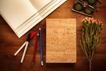 Notebook with plant on wooden table