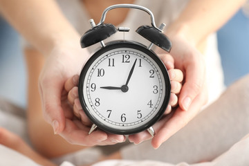 Hands of mother and child with alarm clock, closeup