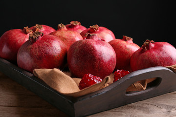 Wooden tray with pomegranates on table