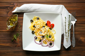 Pasta salad with olives and cheese on wooden background