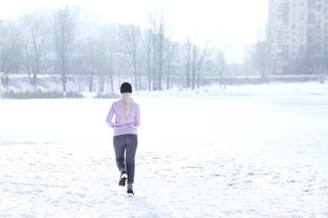 Fototapeta Sportive young woman running in winter park