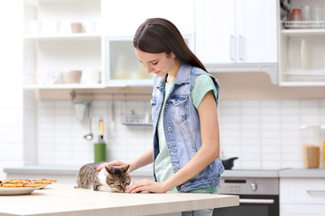 Beautiful young woman and cute cat in kitchen
