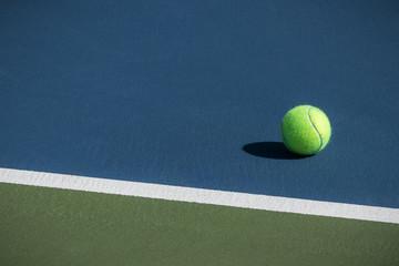 Tennis ball on a blue court