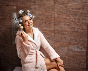 Young attractive housewife in the bathroom. A girl in a bathrobe and curlers doing morning makeup. Makeup Brush. Good morning