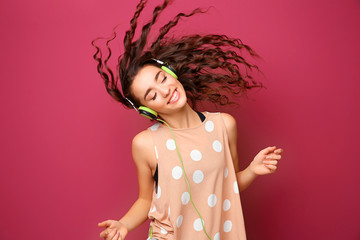 Beautiful young woman in headphones listening to music and dancing on color background