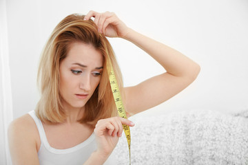 Beautiful young woman measuring length of hair at home
