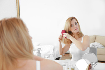 Young woman brushing hair in front of mirror at home