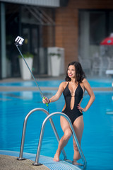 Smiling girl in a black sexy swimsuit posing against swimming pool makes selfie photo with monopod on luxury resort with blurred background
