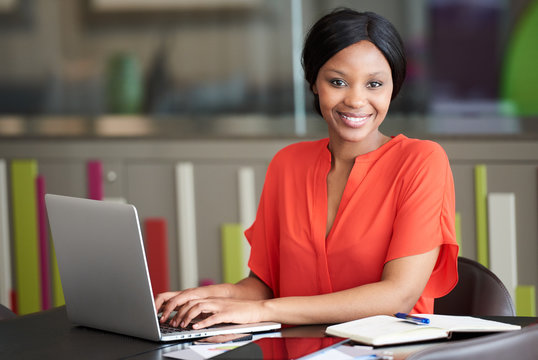 Beautiful well dressed young black businesswoman looking at the camera while sitting at her desk in her colourful office environment, busy typing on her modern laptop computer.