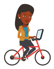 Woman riding bicycle and working on a laptop.