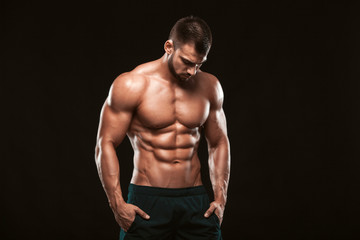 Strong Athletic Man - Fitness Model showing his perfect back isolated on black background with copyspace Wall mural