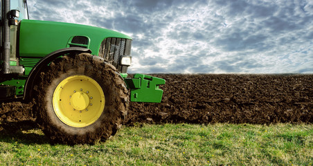 Agriculture. Tractor and cultivated field in the background. Agronomy concept.