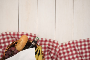 Picnic basket with fruits, bread and red wine