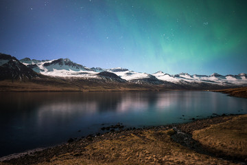 The beautiful Aurora Borealis over the mountains fjord in Stoovarfjorour of East Iceland.