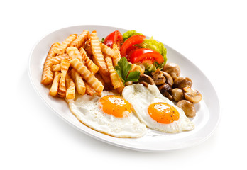 Fried eggs, French fries  and vegetables