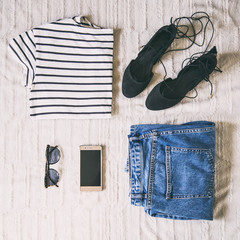 perfect spring outfit accessories. flat lay of a trendy woman fashion outfit. denim jeans, striped shirt, lace up flats, sunglasses and a elegant smartphone. top view.