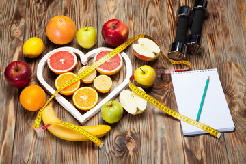 Diet, centimeter and dumbbells on a wooden background