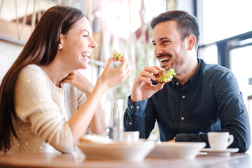Beautiful young couple sitting in a cafe, having breakfast. Love, food, lifestyle