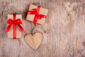 Gift box with a red bow and wooden heart on an old wooden table. Copy space.