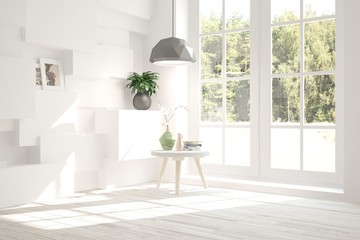 White room with table and green landscape in window. Scandinavian interior design