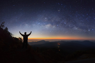 milky way galaxy and silhouette of a standing happy man on Doi inthanon Chiang mai, Thailand.
